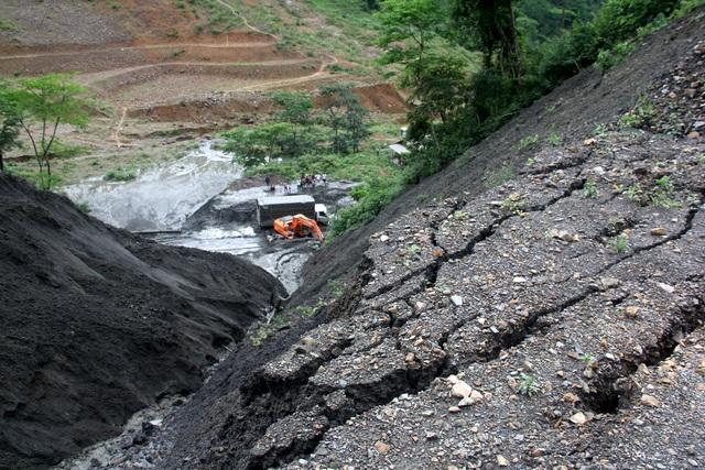 Những rạn nứt của lớp đất đồi ở phía trên cao, có nguy cơ tiếp tục sạt lở khi trời mưa to. Ảnh: Văn Dũng - TTXVN