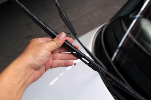 Kéo cần gạt ra khỏi kính chắn gió và giữa chắc để tránh việc vuột tay làm cần gạt đập vào kính chắn gió.