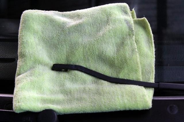 Đặt cần gạt nước lại lên kính chắn gió nhưng bắt buộc phải để một tấm khăn hoặc cao su để tránh vỡ/xước kính.