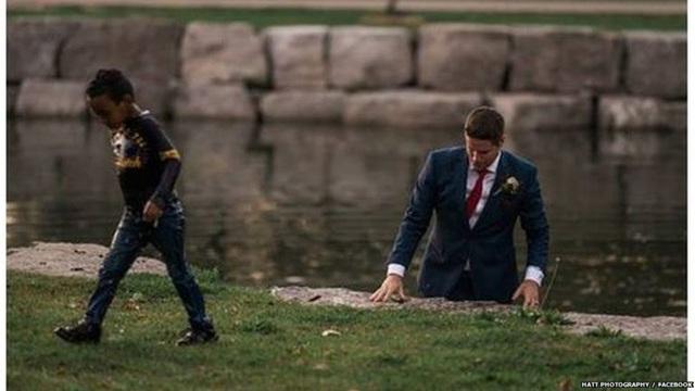 Clayton mặc nguyên bộ vest và lao mình xuống sông cứu bé trai (Ảnh: BBC)