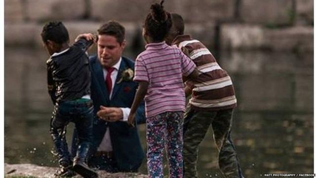 Bé trai được chú rể Clayton đưa lên bờ sau khi bị ngã xuống nước (Ảnh: BBC)