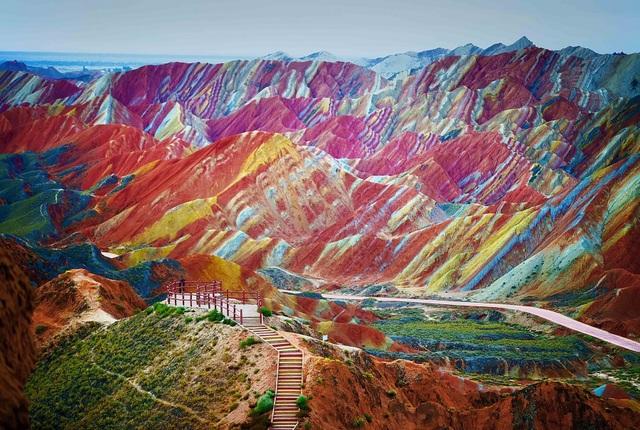 """Có thể bạn không tin nhưng màu sắc sặc sỡ của dãy núi ở trong hình không phải là một sản phẩm photoshop mà là chân thực 100%. Được biết, địa danh này chính là núi cầu vồng nằm tại vùng Zhangye Danxia thuộc tỉnh Cam Túc, Trung Quốc. Theo các nhà khoa học, trong suốt một quá trình dài hơn 24 triệu năm, hàng trăm lớp sa thạch màu và các khoáng chất đã được ép vào với nhau, sau đó vênh lên và tạo thành dãy núi có màu sắc """"đặc biệt"""" như chúng ta thấy ngày nay."""