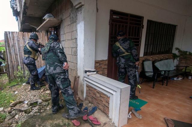 Tham mưu trưởng quân đội Philippines Eduardo Ano cho biết liên minh các nhóm phiến quân thân tổ chức Nhà nước Hồi giáo tự xưng (IS) tiếp tục chiếm quyền kiểm soát ở khu vực trung tâm thành phố, tương đương 10% diện tích của Marawi. Trong ảnh: Một nhóm cảnh sát và binh lính quân đội lục soát từng ngôi nhà để truy lùng các tay súng phiến quân ở Marawi. (Ảnh: Reuters)