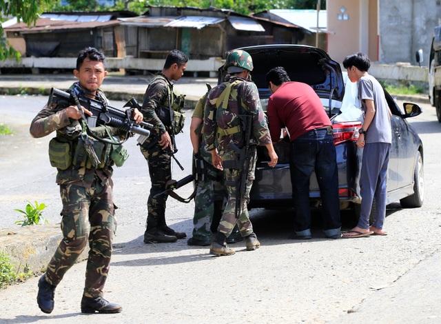 """""""Số hỏa lực được bắn ra từ phía đối phương không còn nhiều như trước. Có những khu vực từng diễn ra nhiều hoạt động của phiến quân thì nay dường như đã giảm bớt lại. Các vụ bắn tỉa cũng ít hơn"""", Tướng Padilla cho biết, nhưng cũng thừa nhận rằng vẫn còn 3 ngôi làng trong thành phố hiện đang bị nhóm khủng bố chiếm đóng. Trong ảnh: Các thành viên của Lực lượng đặc nhiệm Cảnh sát quốc gia Philippines làm việc tại một chốt kiểm tra ở Marawi."""