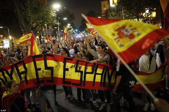 Những người ủng hộ thống nhất mang cờ và khẩu hiệu tuần hành trên đường phố Barcelona (Ảnh: AP)