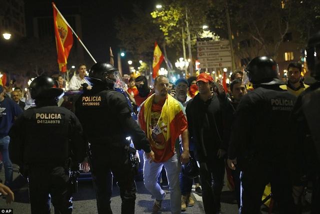 """Bạo loạn đã nổ ra trên đường phố Barcelona giữa nhóm những người ủng hộ chính phủ Tây Ban Nha và nhóm ủng hộ ly khai. Các đoạn video ghi lại cho thấy những hình ảnh """"thượng cẳng chân, hạ cẳng tay"""" giữa những người thuộc 2 nhóm tư tưởng khác nhau. Thông tin ban đầu cho biết đã có 2 người đàn ông bị thương và con số thương vong được cho là cao hơn. (Ảnh: AP)"""