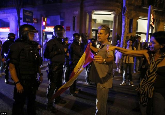 Công tố viên hàng đầu Tây Ban Nha giấu tên cảnh báo, những người có liên quan tới tuyên bố độc lập ở Catalonia có thể phải chịu hình phạt tù tới 25 năm vì hàng loạt cáo buộc phạm pháp. Nhà vua Tây Ban Nha Felipe VI cũng đã lên tiếng chỉ trích hành động của chính quyền Catalonia. Trong ảnh: Một người đàn ông cầm cờ Tây Ban Nha đứng trước cảnh sát Catalonia. (Ảnh: AP)