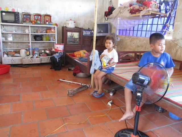 Ông Nguyễn Văn Khảm cùng hai cháu mình đang tá túc tại một phòng học sau khi bị thủy thần nuốt mất nhà