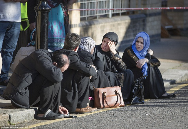 Những cư dân may mắn chạy thoái khỏi tòa nhà bị cháy chờ tin tức bên ngoài tòa nhà (Ảnh: LNP)