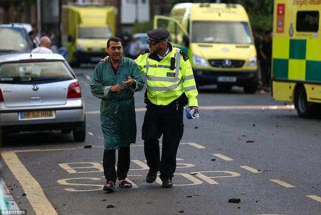 Cảnh sát trò chuyện cùng một cư dân của tòa nhà Grenfell (Ảnh: Reuters)