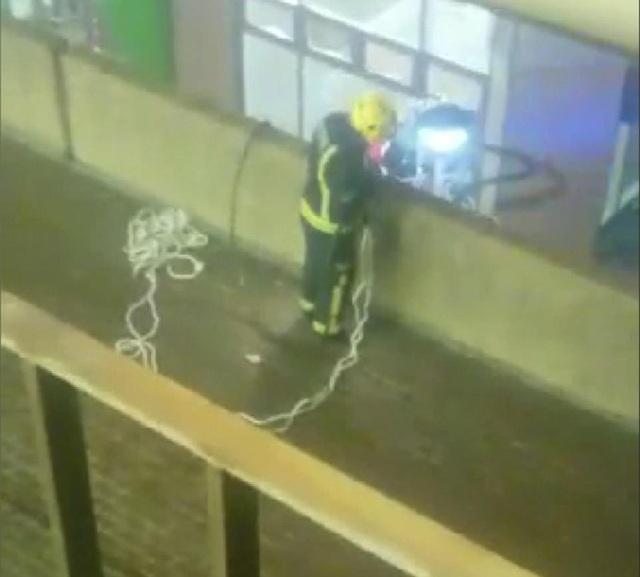 Một lính cứu hỏa tìm cách cứu người dân mắc kẹt tại hiện trường vụ cháy.