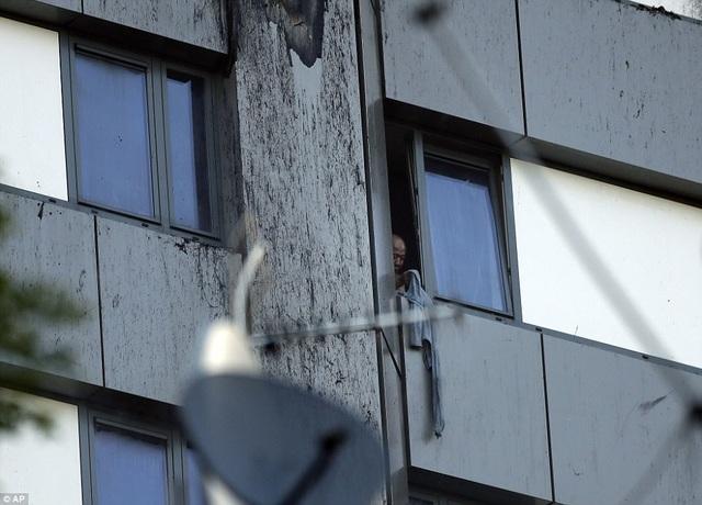 Một cư dân trong tòa tháp dùng áo để ra dấu hiệu cho lực lượng cứu hỏa (Ảnh: AP)