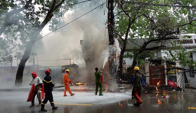 Lực lượng chức năng mặc áo mưa khống chế đám cháy.