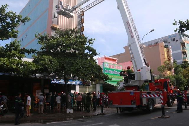 Lực lượng chức năng dùng xe thang dập đám cháy trên tầng 2.