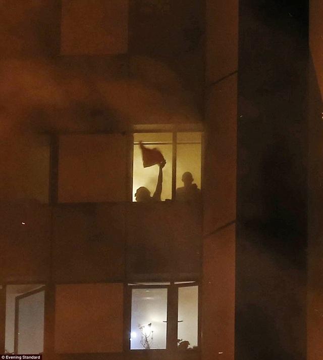 Nhiều người mắc kẹt trong tòa nhà tìm cách ra hiệu cho lực lượng cứu hộ. (Ảnh: Evening Standard)