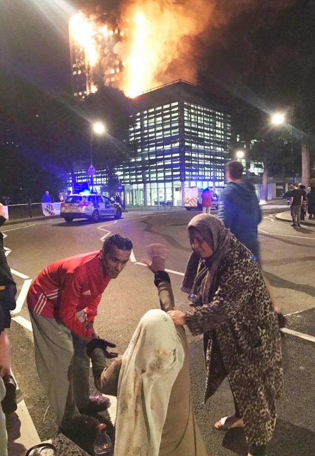 Một nạn nhân sau khi thoát ra ngoài vẫn bàng hoàng vì căn hộ bốc cháy. (Ảnh: EPA)