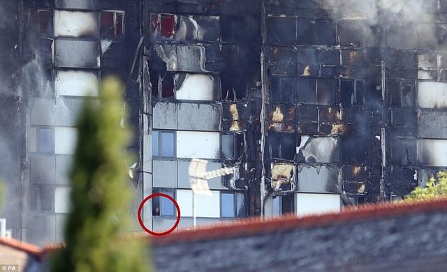 Một người đàn ông mắc kẹt trong tòa nhà cầu cứu. (Ảnh: PA)