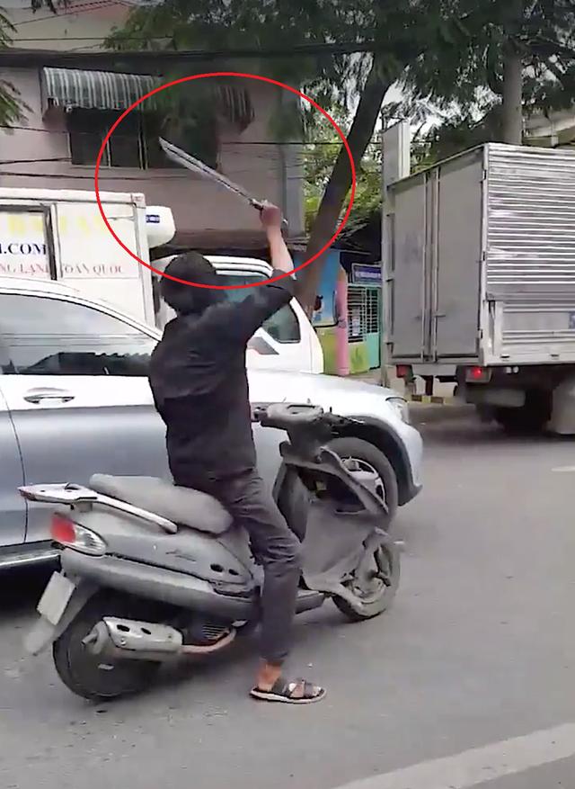 Thanh niên cầm mã tấu chém hàng loạt kính chiếu hậu của ô tô trên đường (ảnh cắt từ clip)
