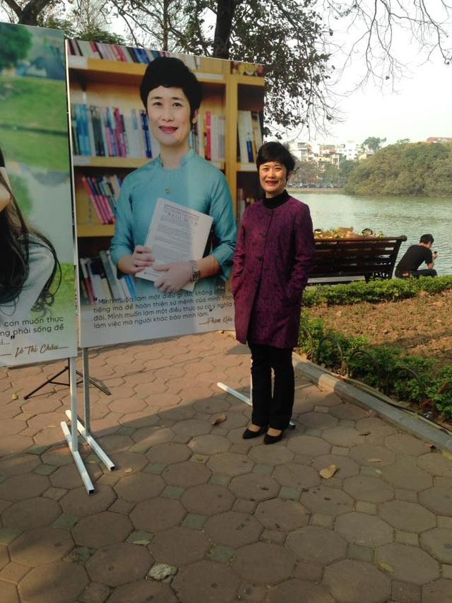 Bà Phạm Kiều Oanh đứng bên cạnh bức chân dung của mình.