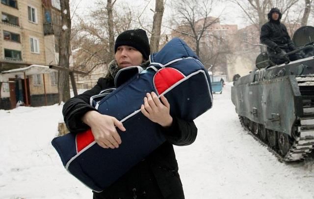 Một phụ nữ bế một em bé đi sơ tán tại Donetsk, Ukraine. (Ảnh: Reuters)