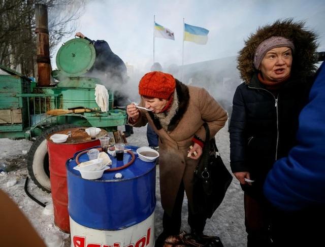 Một phụ nữ đứng ăn giữa trời lạnh trung tâm tạm trú. (Ảnh: Reuters)