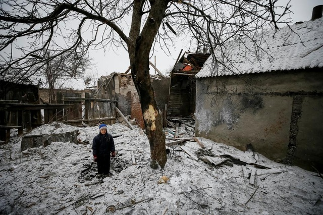 Bé Lesha, 8 tuổi, đứng giữa khu vực bị tàn phá do xung đột ở miền Đông Ukraine. (Ảnh: Reuters)