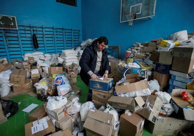 Một tình nguyện viên sắp xếp hàng cứu trợ tại một trung tâm tạm trú ở thị trấn Avdiyivka. (Ảnh: Reuters)
