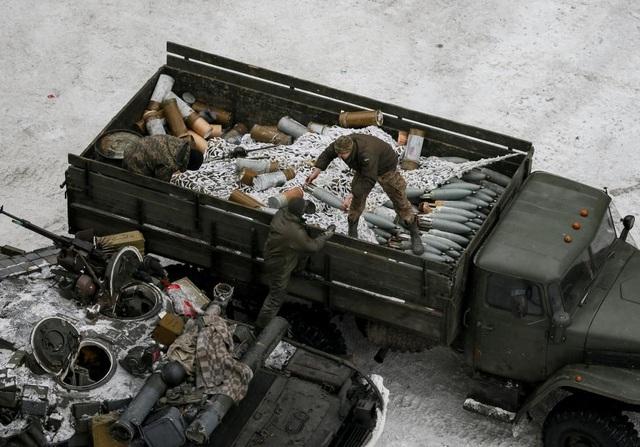 Các thành viên của lực lượng chính phủ Ukraine vận chuyển vũ khí lên xe tăng tại thị trấn Avdiyivka. (Ảnh: Reuters)