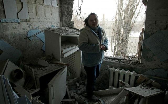 Một phụ nữ thất thần khi đứng trong căn hộ chung cư bị phá hủy, mà người dân địa phương nói là do một vụ pháo kích gần đây tại thành phố Donetsk do phe đòi độc lập kiểm ở Đông Ukraine. (Ảnh: Reuters)