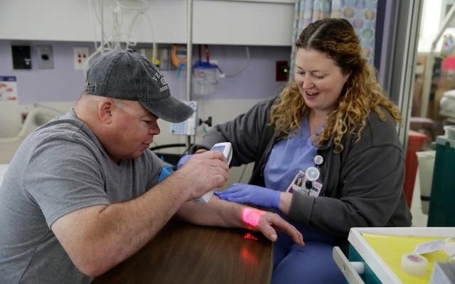 Brian Madeux, 44 tuổi, sử dụng một thiết bị hồng ngoại để quan sát tĩnh mạch của mình khi nữ y tá Siobhan Field chuẩn bị đường truyền tĩnh mạch cho liệu pháp chỉnh sửa gen đầu tiên trên cơ thể người.