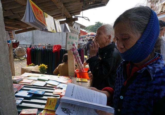 Các cụ già đang chọn sách tử vi để tự mình dự đoán vận mệnh của gia đình trong năm mới.