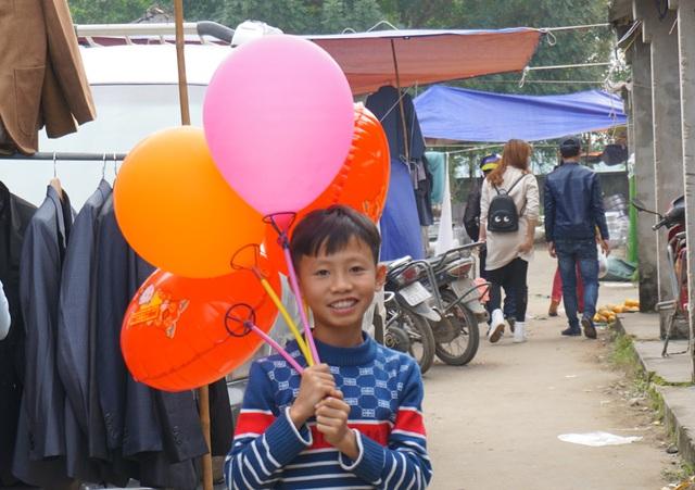 Trong khi đó, những đứa trẻ đến với phiên chợ Dinh cuối năm để bán bóng bay, kiếm tiền Tết phụ bố mẹ.