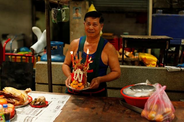 Một người đàn ông dâng lễ cúng nhân dịp năm mới tại một khu chợ ở Bangkok, Thái Lan. (Ảnh: Reuters)