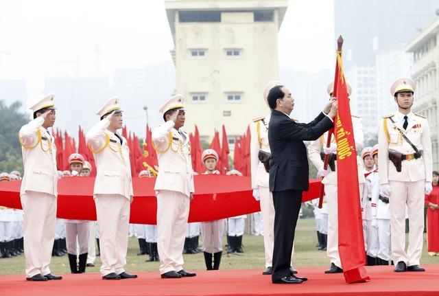 Chủ tịch nước Trần Đại Quang gắn Huân chương Chiến công hạng Nhất lên cờ truyền thống của đơn vị. Ảnh: Nhan Sáng-TTXVN
