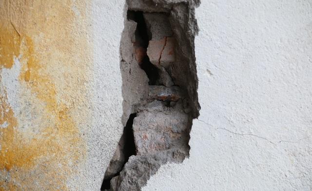 Một phần tường của ngôi nhà bị nứt, lộ sắt ra ngoài.