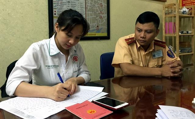 Thiếu úy Quân hướng dẫn chị Mai chứng minh chiếc điện thoại là của mình, làm thủ tục để nhận lại.