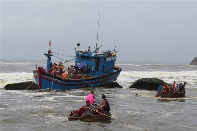 Lực lượng chức năng cùng ngư dân đang cứu nạn tàu cá bị sóng xô vào đá ở cửa biển Mỹ Á. Ảnh: PV