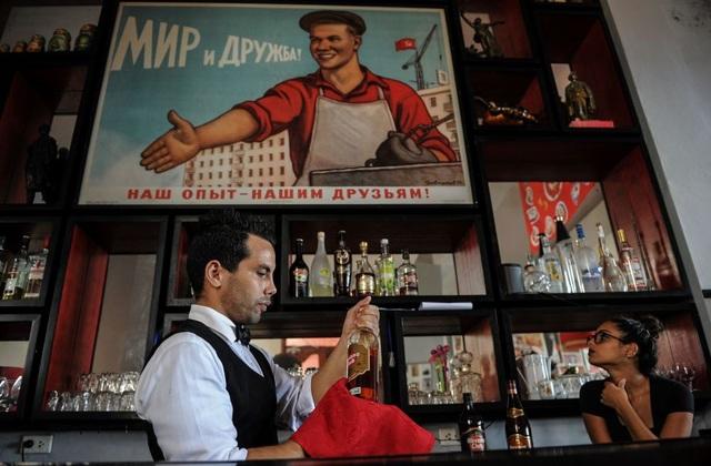 """Gần 30 năm sau khi Liên Xô tan rã, Cuba vẫn lưu giữ nhiều """"di sản"""" mang dấu ấn Liên Xô tại nước này, từ tên của người dân và các mối quan hệ gia đình, cho tới các loại phương tiện, công trình xây dựng, trường học, công viên, thậm chí cả vũ khí. Trong ảnh: Một nhân viên pha chế làm việc bên trong một nhà hàng được bài trí theo phong cách Liên Xô tại thủ đô Havana, Cuba."""