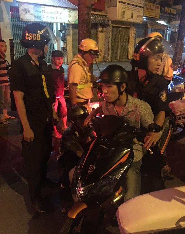Cảnh sát áp giải nghi can về trụ sở công an