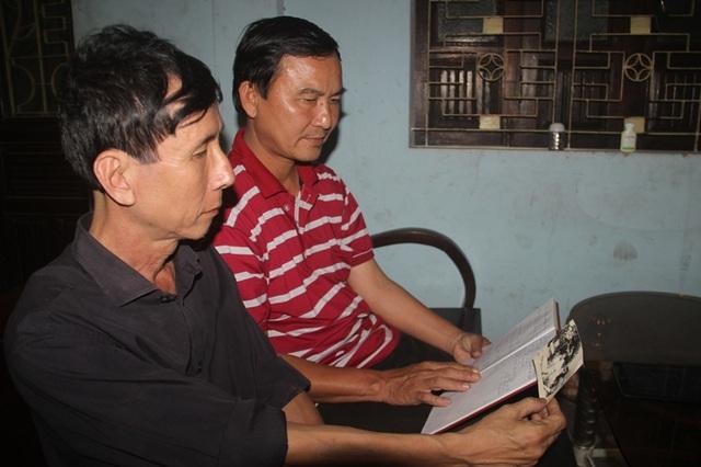 Hai cựu binh Trần Thiên Phụng và Võ Văn Doàn (áo đỏ) xem lại kỷ vật là bức ảnh của đồng đội đã hy sinh