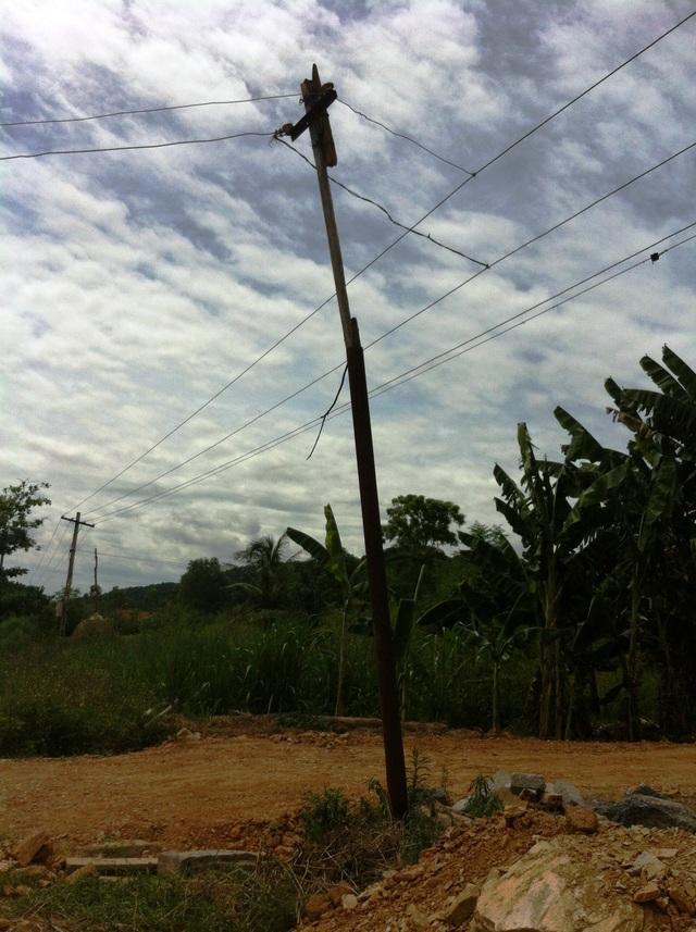 Một cây cột điện bằng sắt với đường dây điện được móc nối tạm bợ. Trong khi đó, hệ thống đường dây dẫn hiện vẫn là dây trần.