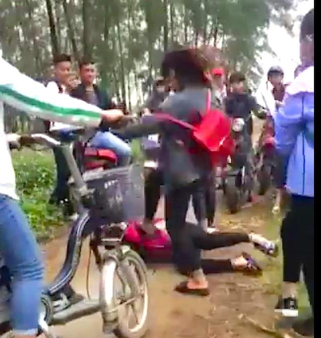 Nhóm nữ sinh dùng chân đánh nữ sinh nằm dưới đất.