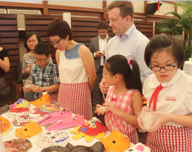 Đại sứ Bertrand Lortholary quan sát những chiếc mặt nạ do chính tay các em nhỏ vẽ theo trí tưởng tượng của mình.