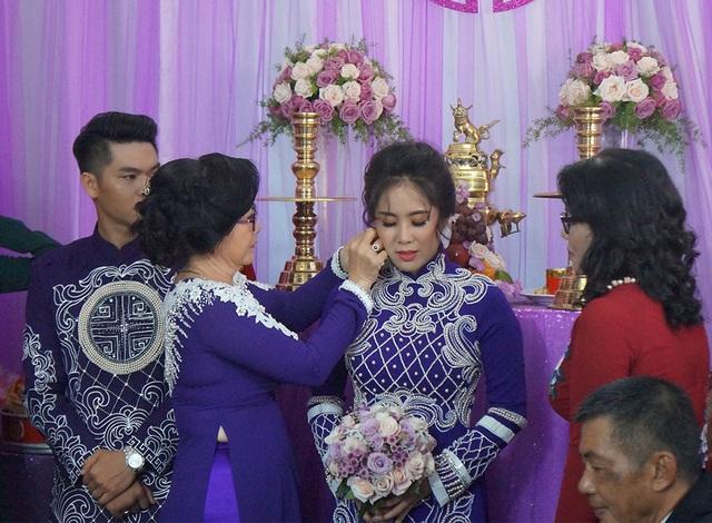 Mẹ cô dâu đeo bông tai cho con gái theo phong tục truyền thống trong hôn nhân.
