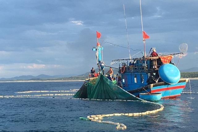 Một chiếc tàu cá đang kéo lưới trên biển.