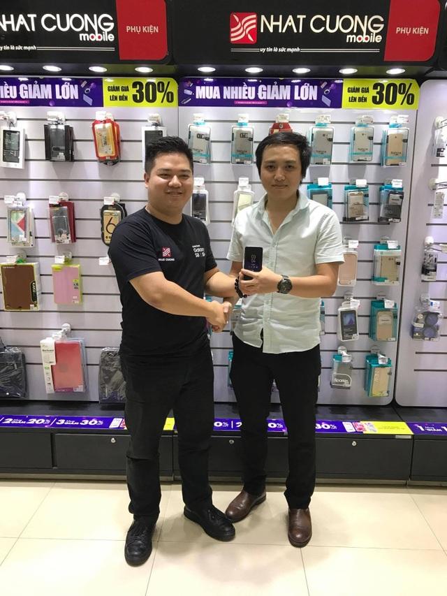 Anh Nguyễn Thành Trung, phụ trách truyền thông Nhật Cường Mobile (trái) trao sản phẩm Samsung Galaxy S8 đến khách hàng chốt giá cao nhất tại buổi đấu giá từ thiện