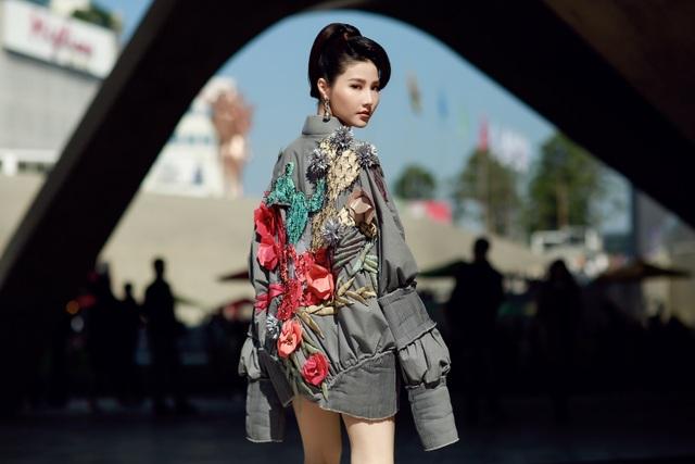 """Thiết kế bomber giấu quần tạo nên điểm nhấn và độ nổi bật cho người đẹp. Vóc dáng mảnh mai của cô càng được tôn lên trong thiết kế """"quá khổ"""" và ống tay dài. Tông xám bạc kết hợp cùng những chi tiết thêu ở phía sau lan ra sau thân áo vô cùng phù hợp với không gian hiện đại của một góc Seoul."""