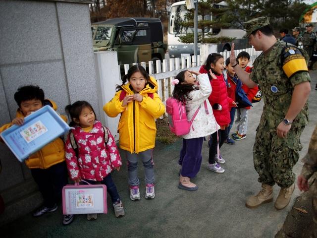 """Trường tiểu học Daesungdong tọa lạc tại Làng Tự do Taesung, phía Nam của đường ranh giới phân chia lãnh thổ Triều Tiên và Hàn Quốc, tại Khu vực phi quân sự liên Triều (DMZ). Nơi đây, vào năm 1993, cựu Tổng thống Mỹ Bill Clinton đã gọi là """"khu vực đáng sợ nhất trên trái đất"""". Ở phía Nam của DMZ là nơi quân Mỹ đồn trú. Họ chỉ mất 5 phút lái xe tới trại do Liên Hợp Quốc thành lập để theo dõi tình hình Triều Tiên. Trong ảnh: Binh sĩ Mỹ đập tay với các học sinh."""