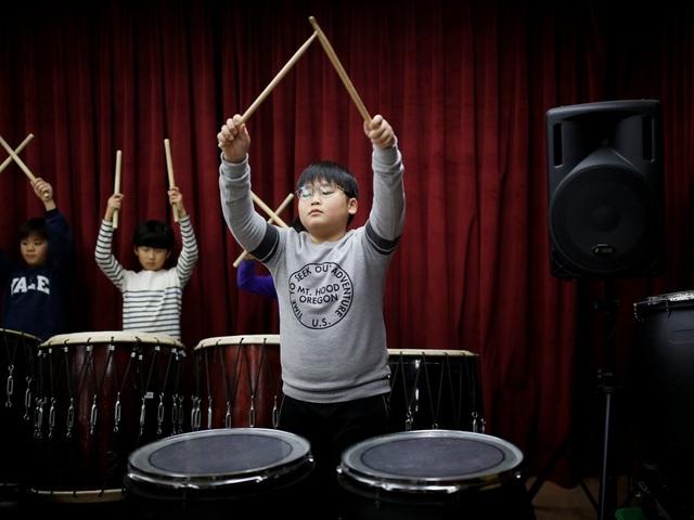 Những đứa trẻ ở đây học tập bình thường như những đứa trẻ ở trường tiểu học khác. Trong ảnh: Một bé trai đang tập trống.