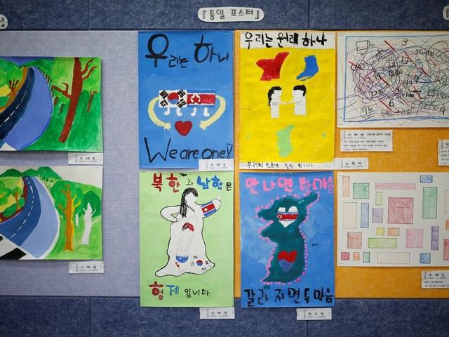 Các học sinh vẽ tranh với thông điệp mong ước 2 miền Triều Tiên sớm hòa hợp treo trên tường ngôi trường.